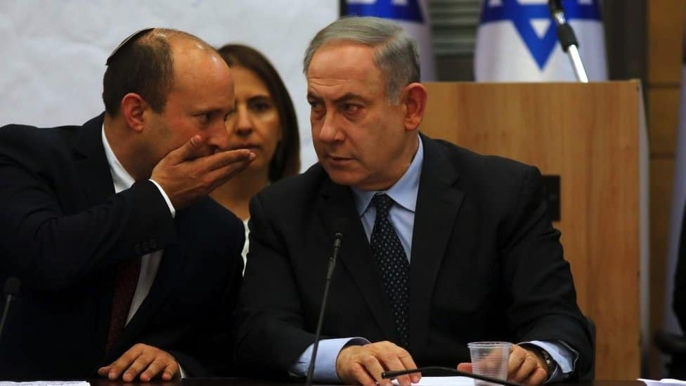 Naftali Bennett (L) whisteprs to Prime Minister Benjamin Netanyahu (R) duing a meeting of the Israeli right-wing block, at the Knesset.