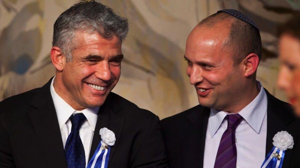 Israeli politician Yair Lapid (L), leader of the Yesh Atid party, speaks to Naftali Bennett (R)