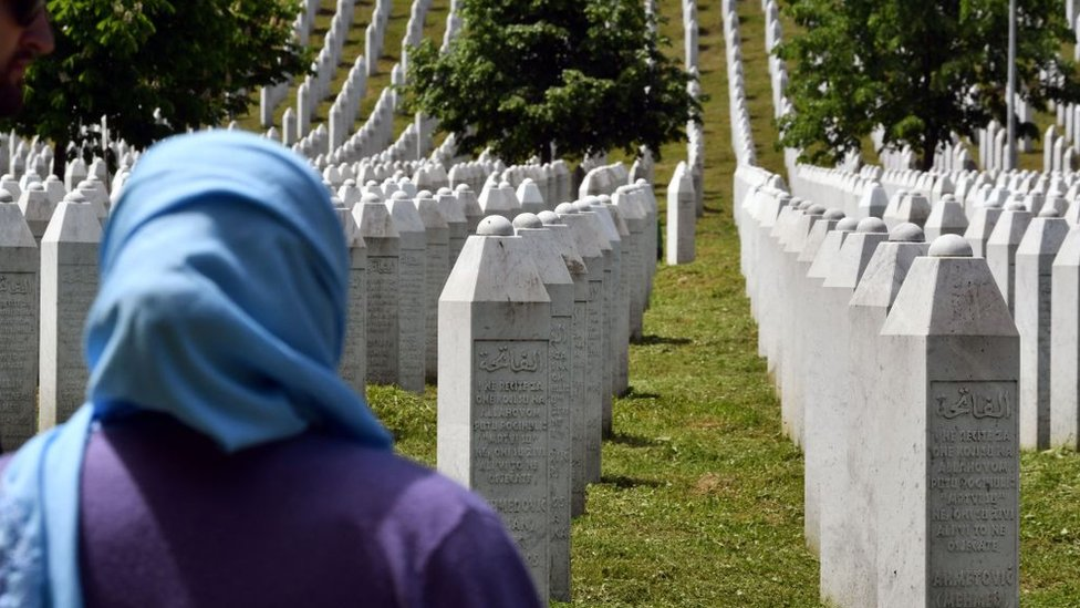 A woman stands near tombstones at a cemetery to honour the victims of the 1995 Srebrenica massacre