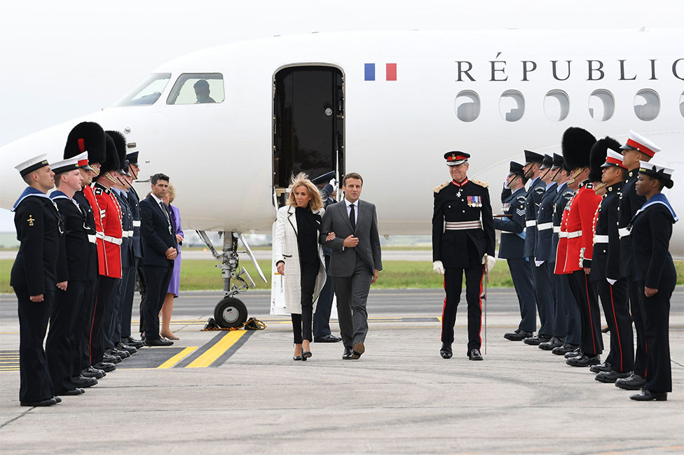 French president Emmanuel Macron and his wife Brigitte Macron step off their plane and are greeted by members of the Navy and Armed Forces