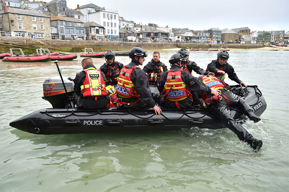 Police officers are seen on a rigid inflatable boat in St Ives in the sea