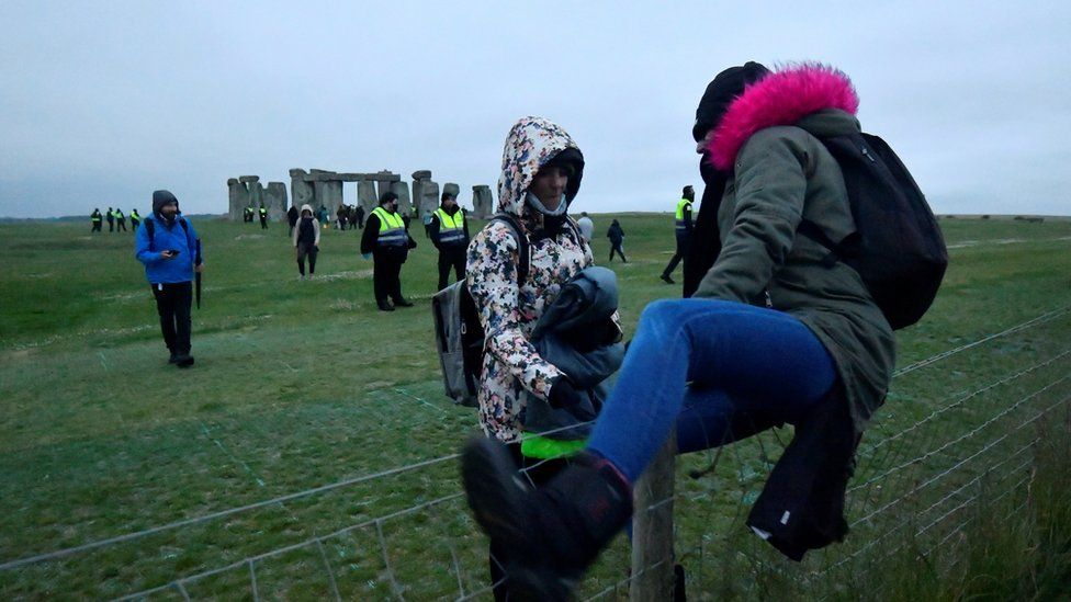 Revellers climb over a fence to get into Stonehenge ancient stone circle, despite official events being cancelled amid the spread of the coronavirus disease (COVID-19), near Amesbury, Britain, June 21, 2021.