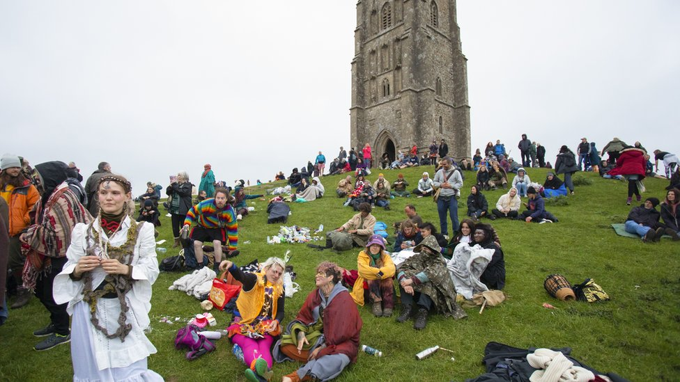 Revellers gather to celebrate the summer solstice on Glastonbury Tor, Somerset,