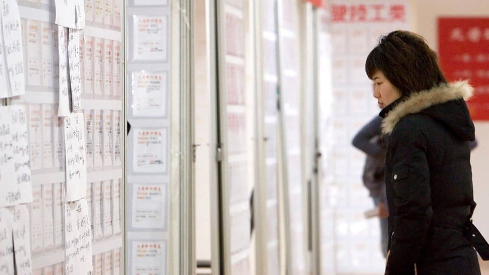 A job-seeker looks at employment ads on billboards in Tiantian job fair in Shanghai, China.