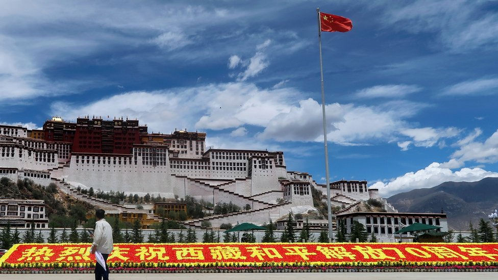 Dvorec Potala. Okolo nego ustanovlen kitaйskiй flag i znak v čestь 70-letiя ustanovleniя Kitaem kontrolя nad Tibetom.