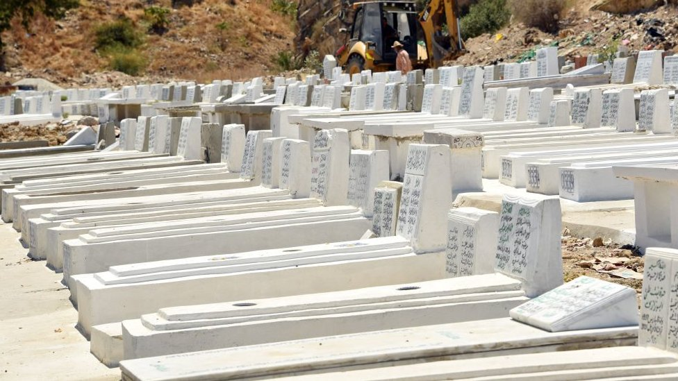 Gravediggers are seen working on a grave at the El Jalez cemetery in Tunisia