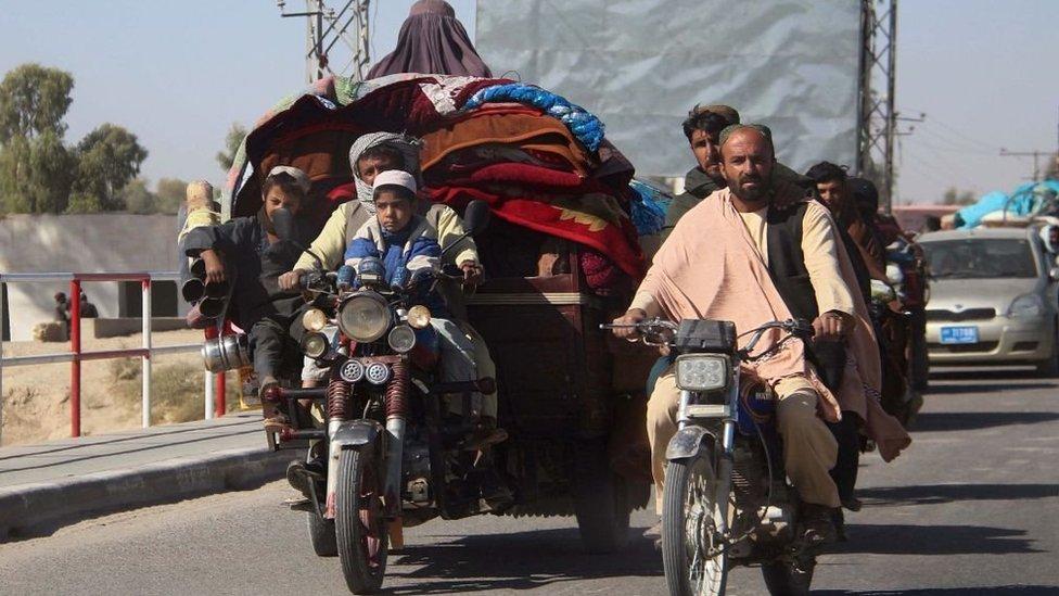 Ljudi na vozilima nose ćebad i tepihe