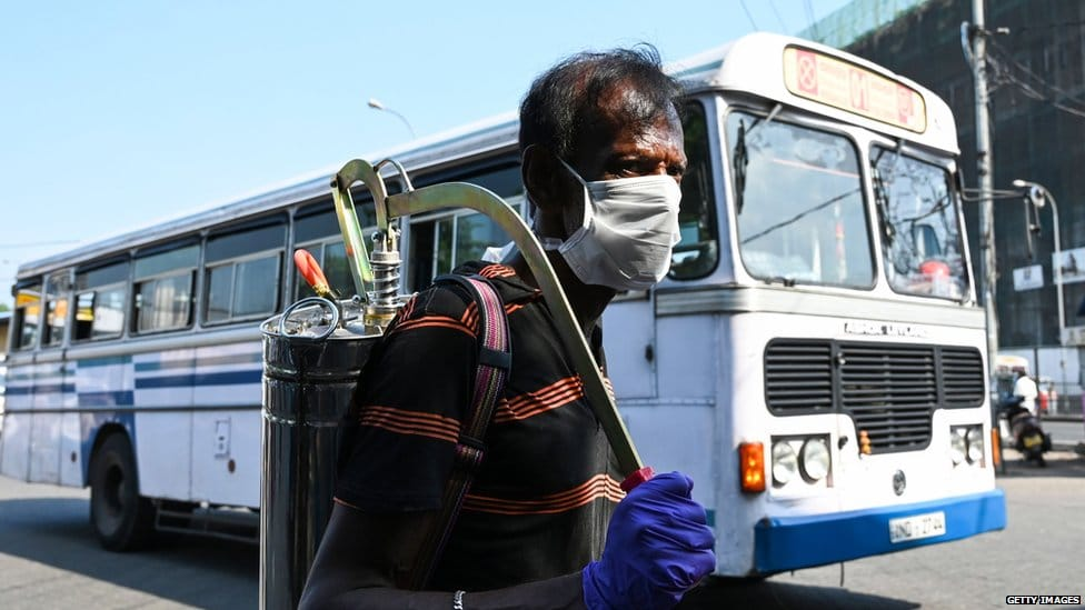 A worker sprays disinfectant to sanitize a bus station