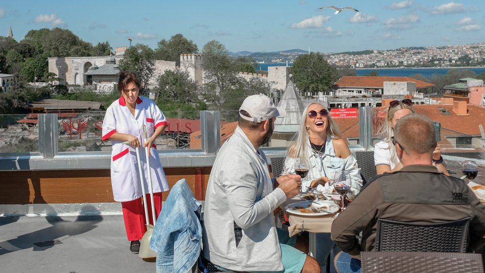 A group of tourists enjoy a meal in Istanbul while a cleaner is standing nearby