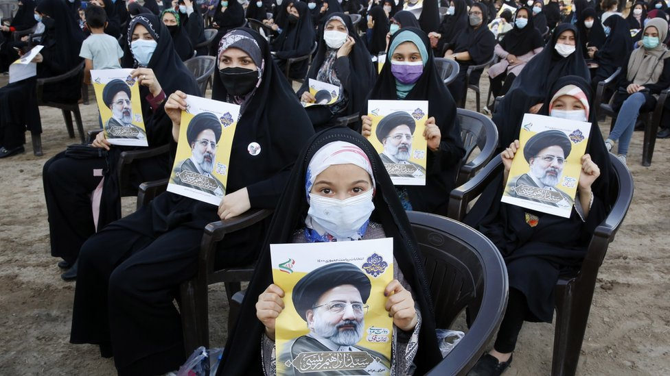 Supporters of Iranian presidential candidate Ebrahim Raisi hold pictures of him at an election rally in Eslamshahr, Iran (6 June 2021)
