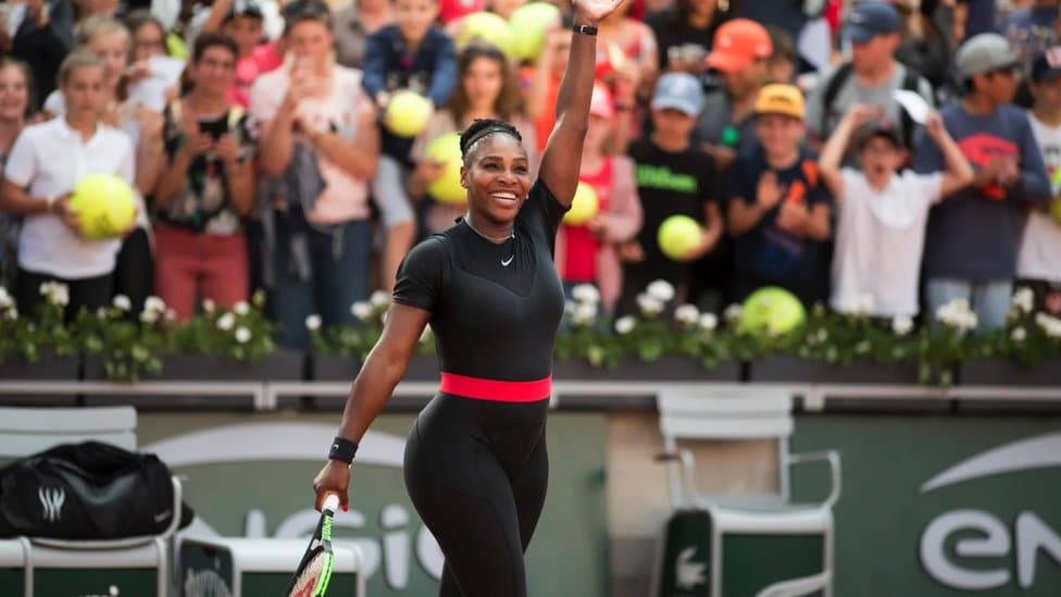 Serena Williams in a black catsuit with a red band at the waits at the 2018 French Open.