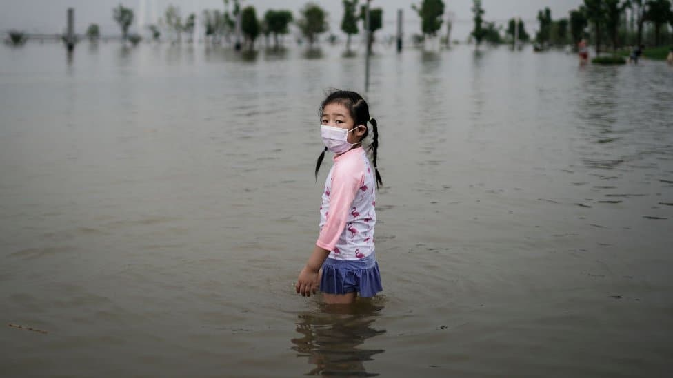 A little girl wearing a mask at a flooded street in China