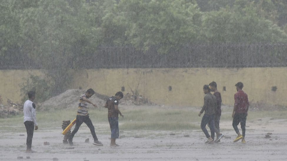 Boys play cricket on the street in Delhi under heavy rain in June 2021