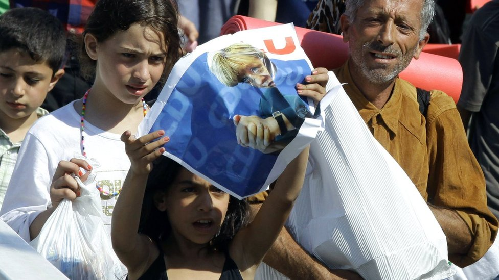 A migrant girl holds a poster of German Chancellor Angela Merkel as migrants walk in Budapest downtown after leaving the transit zone of the main train station, on September 4, 2015