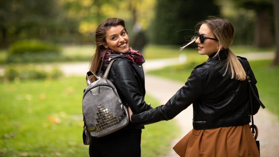 Two women walk away from the camera smiling