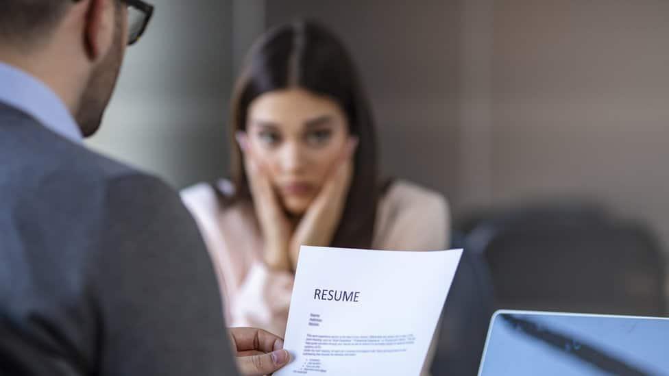 Una mujer joven en una oficina parece preocupada mientras un hombre lee su currículum