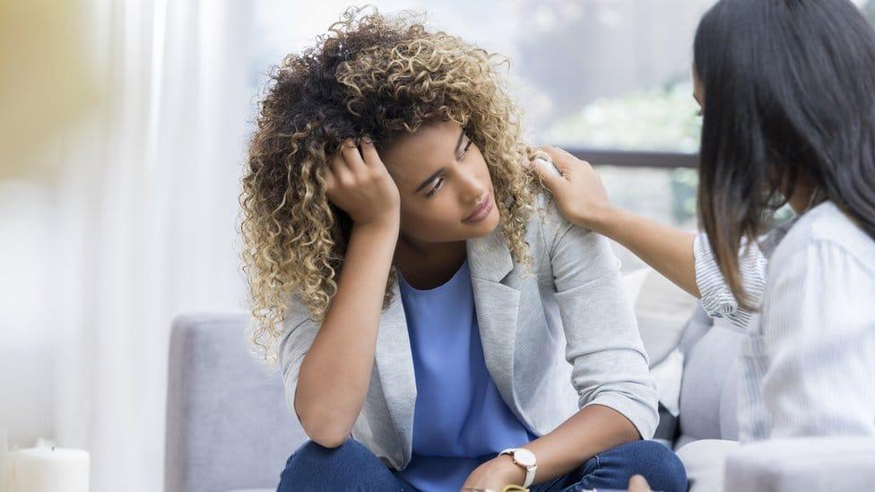 Una mujer en una oficina consuela a un colega