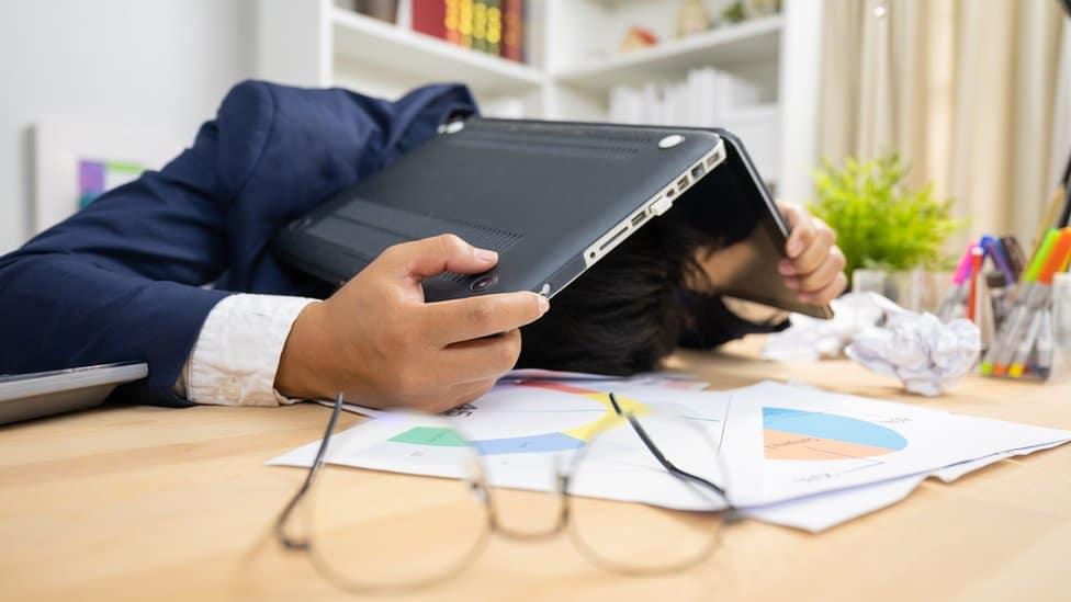 Un hombre sostiene una computadora sobre su cabeza en un escritorio