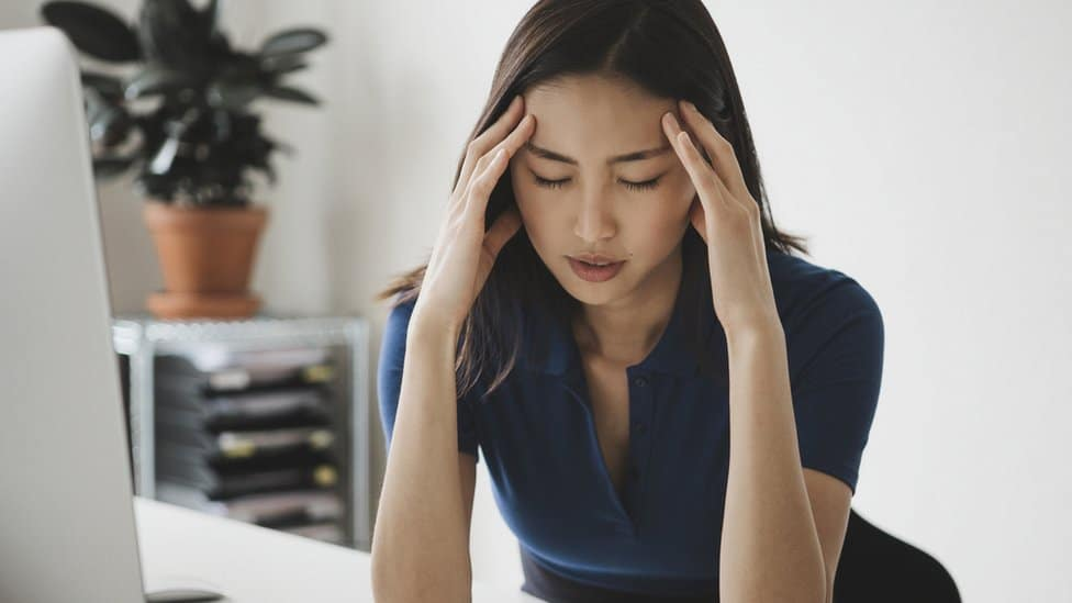 A young female office worker appears stressed