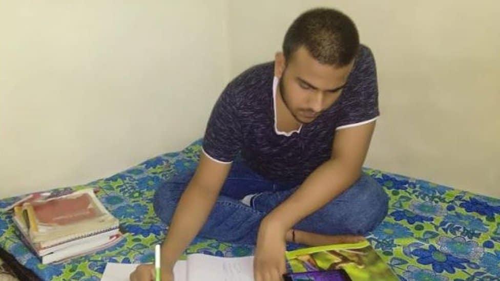 Kumar leyendo en su casa
