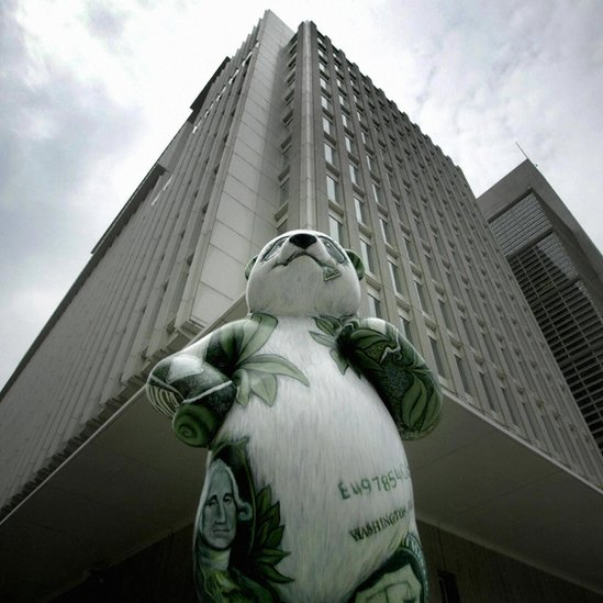 A statue of a panda painted with bamboo leaves and dollar bills outside an office building