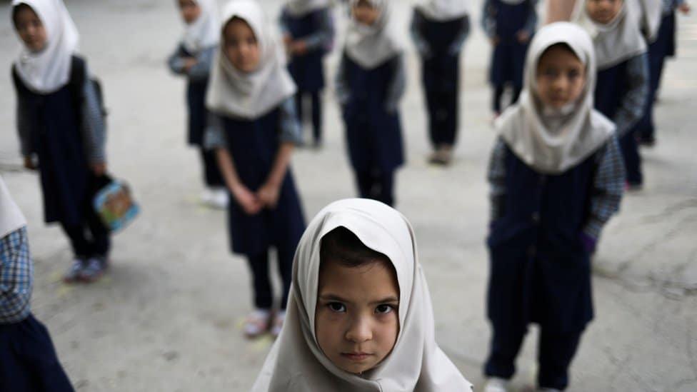 Afghan girls look on at a school in Kabul, Afghanistan