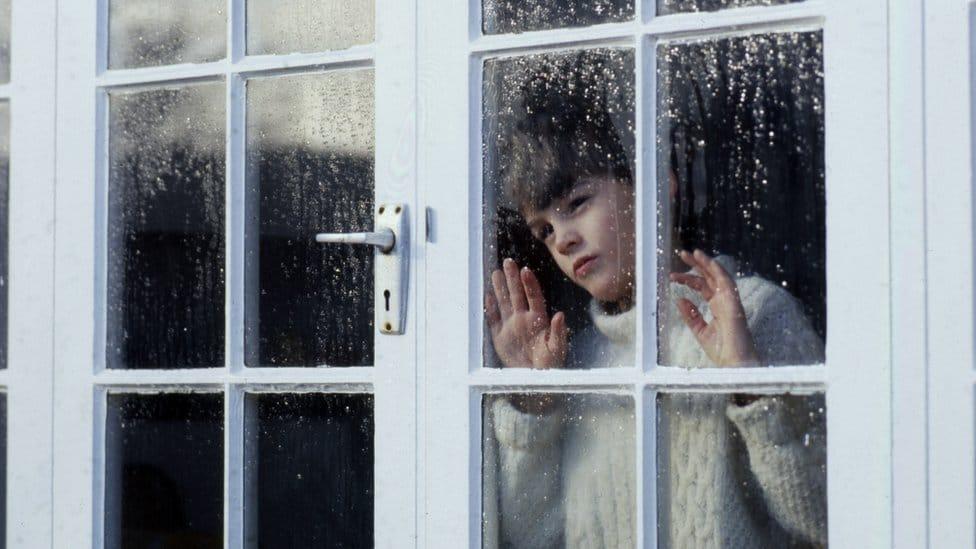 Dečak posmatra kišni dan kroz prozor