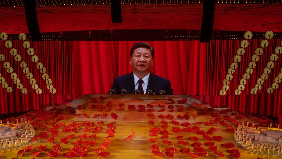 Chinese President and Chairman of the Communist Party Xi Jinping appears on a large screen as performers dance during a mass gala marking the 100th anniversary of the Communist Party on 28 June 2021.
