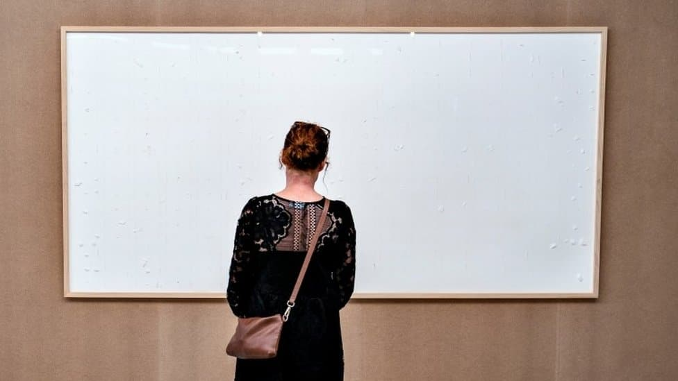 A woman looks at an art installation titled Take the Money and Run by Danish artist Jens Haaning