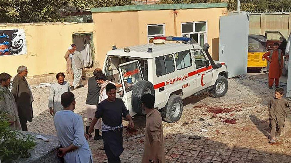 Afghanische Männer stehen nach einem Bombenanschlag auf eine Moschee in Kunduz . neben einem Krankenwagen